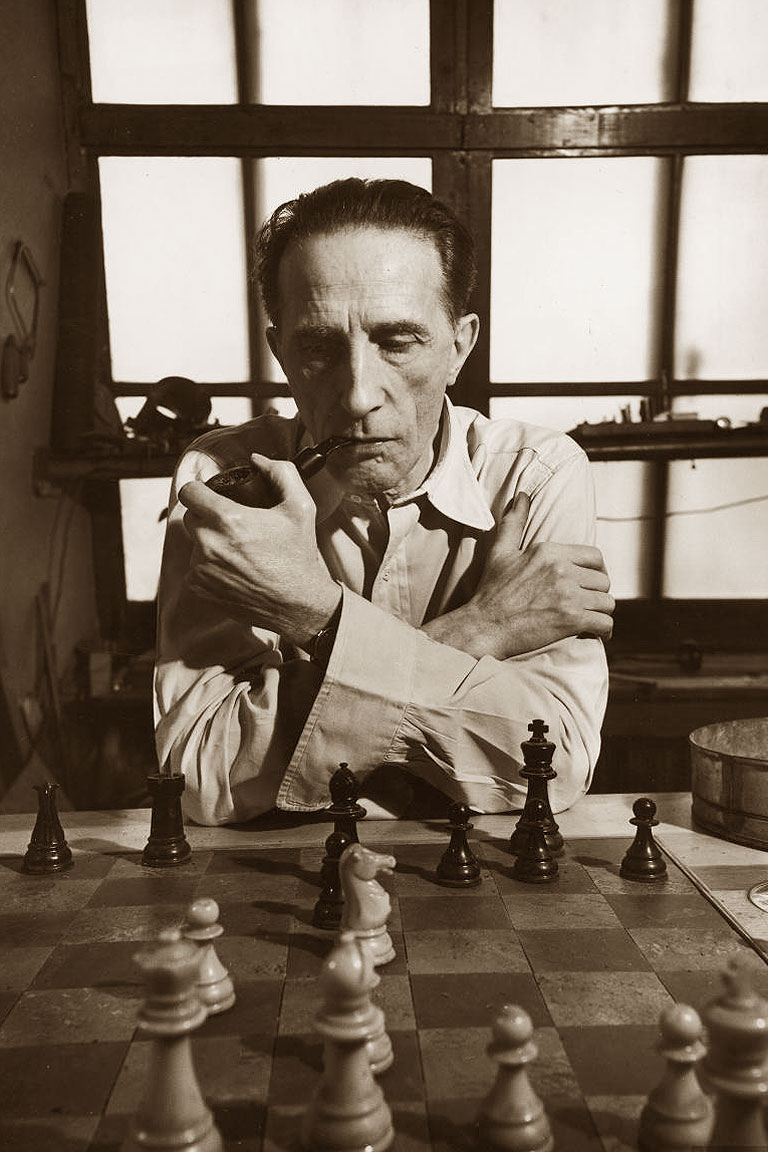 Foto di Marcel Duchamp davanti a una scacchiera con la sua pipa